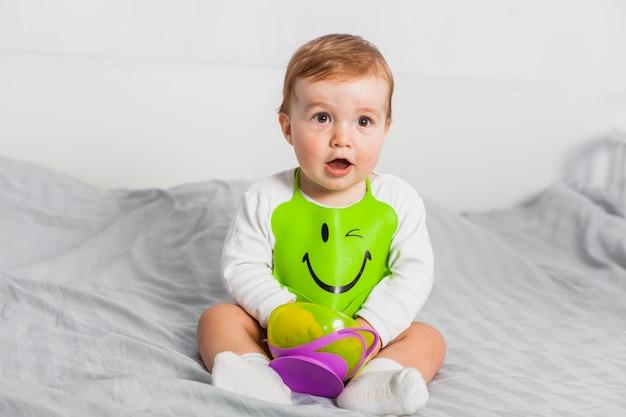 Sitting baby wearing bib