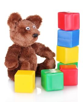 白で隔離のクマのおもちゃとカラーキューブを座って