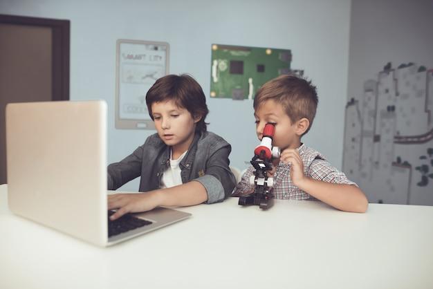 집에서 노트북과 현미경을 사용하는 앉아있는 소년.