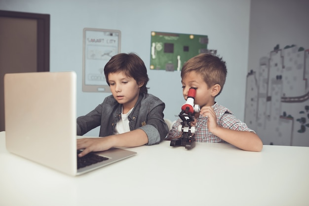 Sitting boys using laptop and microscope at home.