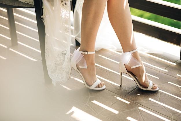 ウェディングドレスとハイヒールを履いて座っている花嫁