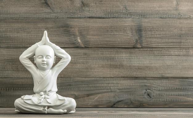 仏陀に座っています。木製の背景に白い僧侶像。瞑想。リラックス。レトロなスタイルのトーンの写真