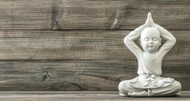 仏陀に座っています。木製の背景に白い僧侶像。ヴィンテージスタイルのトーンの写真