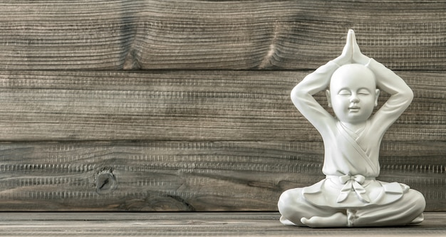 Sitting buddha. white monk statue on wooden background. vintage style toned picture