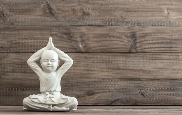 仏陀に座っています。木製の背景に白い像。瞑想