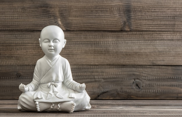 Сидящий будда. белая статуя на деревянном фоне. расслабляющая концепция