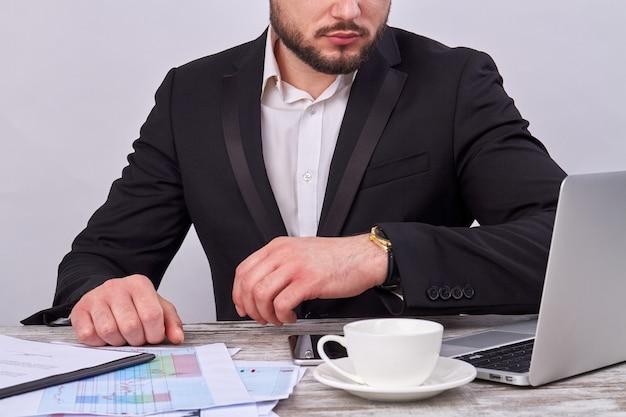 Сидящий бизнесмен с ноутбуком и чашкой кофе