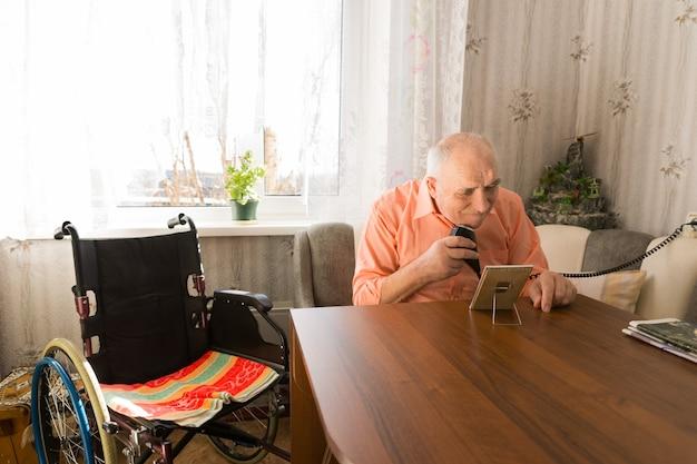 휠체어 옆에 앉아 전기 면도기로 수염을 면도하는 노인 앉아 있습니다.