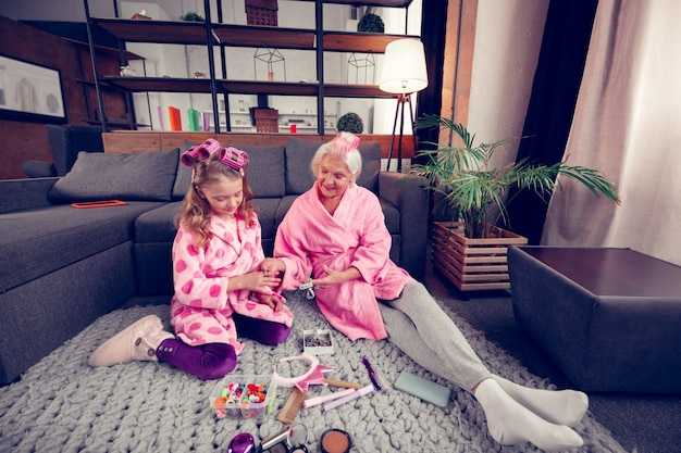 Sitting on floor. cute good-looking granny and girl in bathrobes sitting on floor and choosing hairpins