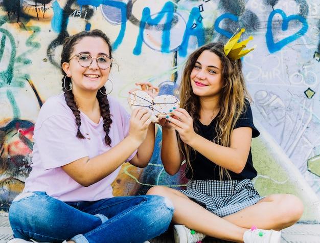 Amici seduti con palloncini e torta di compleanno