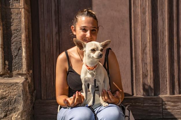 Сидящая девушка в углу города с чихуахуа