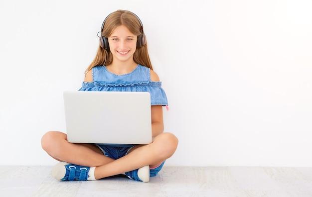 白のノート パソコンとヘッドフォンで座っている女の子