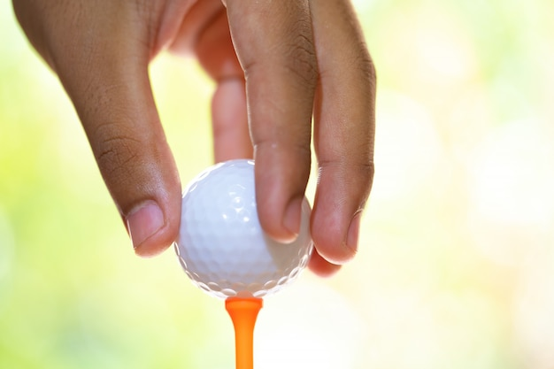 Sitting golf ball on tee and hand to holding ball in golf course