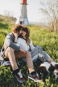 Sitting in grass young stylish hipster couple in love walking with dog in countryside, summer style boho fashion, romantic