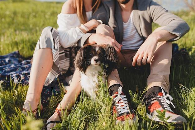 Seduto in erba giovane coppia hipster alla moda innamorata che cammina con il cane in campagna, moda boho stile estivo, romantico