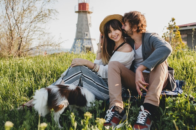 Sitting in grass young stylish hipster couple in love walking with dog in countryside