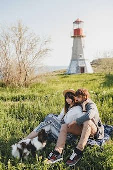Sitting in grass, young stylish hipster couple in love with dog in countryside
