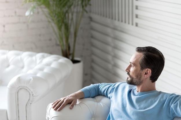 半分の顔に座っています。白いソファに座ってリラックスしながら頭を回す真面目な自信のあるひげを生やした男