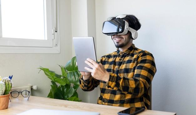 Сидящий красавец использует очки виртуальной реальности, держа перед собой планшет