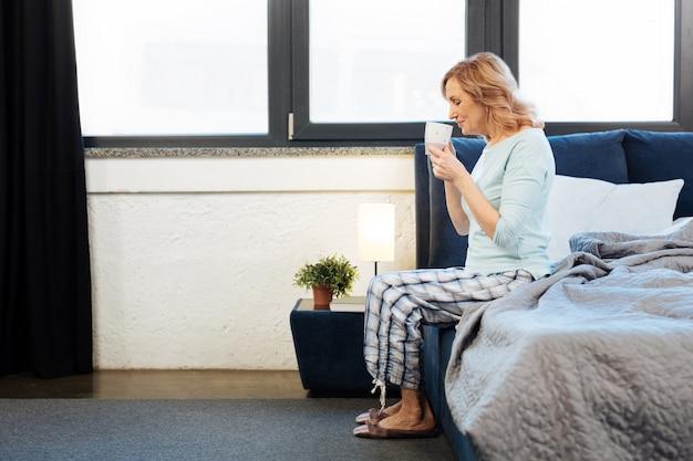 Сидя в спальне. приятная светловолосая зрелая дама сидит на краю кровати и пахнет свежеприготовленным кофе