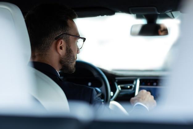 車に座っています。オフィスに運転中に彼の車に座って眼鏡をかけたひげを生やした若い男