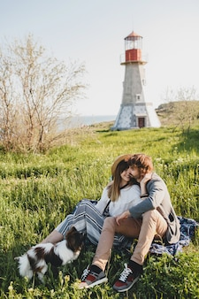 Сидя в траве молодые стильные хипстерские влюбленные пары гуляют с собакой в сельской местности