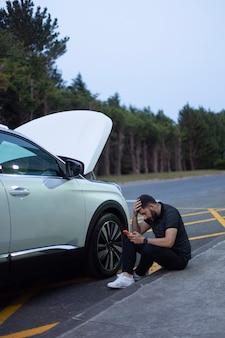 Сидящий мужчина с рукой в голове с помощью смартфона после поломки автомобиля. находится в черной одежде рядом с разбитой белой машиной с открытым капотом, припаркованной у дороги на фоне деревьев.