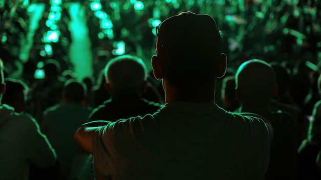 夜に公共の場所でサッカーを見ている座っている男