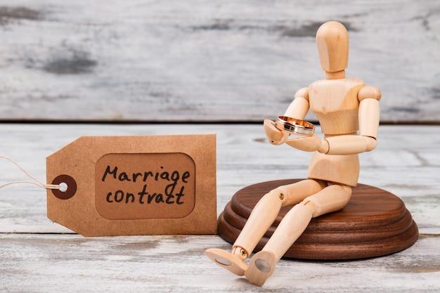 結婚指輪を持って座っているマネキン。結婚契約の概念。