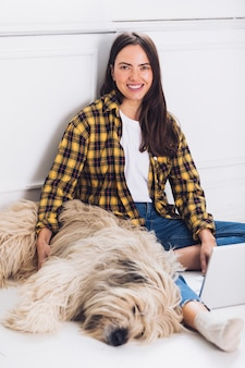 Sitting modern woman with dog