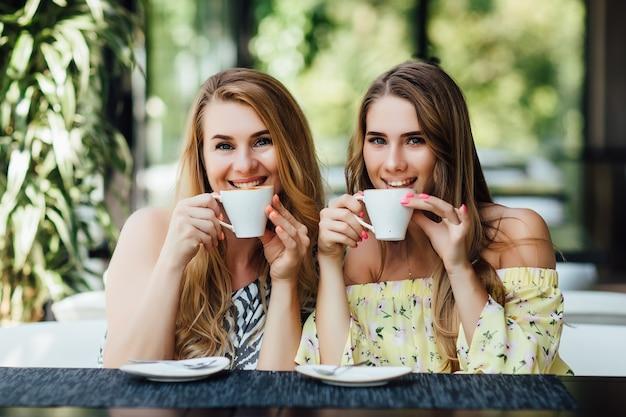 カフェでお茶やカフェを飲む母と娘に座って