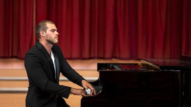 座っているミュージシャンがピアノを弾く
