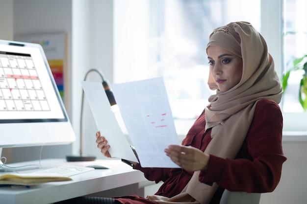 コンピューターの近くに座っています。コンピューターの近くに座って彼女の週のスケジュールをチェックしているヒジャーブを身に着けている暗い目の先生