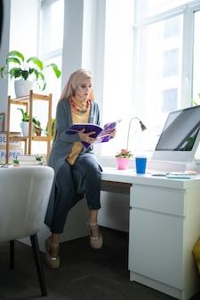 コンピューターの近くに座っています。コンピューターの近くに座って本を読んでヒジャーブを身に着けているスタイリッシュなイスラム教徒の教師