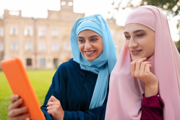 친구 근처에 앉아. 노트북 친구 근처에 앉아 오렌지 태블릿을 들고 파란색 hijab를 착용하는 학생