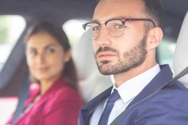 아내 근처에 앉아. 차에 아름다운 사랑하는 아내 근처에 앉아 안경을 쓴 수염 난된 젊은 남자