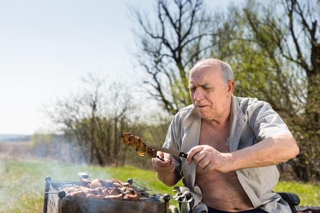 공원에서 바베큐를 하는 동안 막대기에 구운 고기가 잘 익었는지 확인하는 노인 앉아.