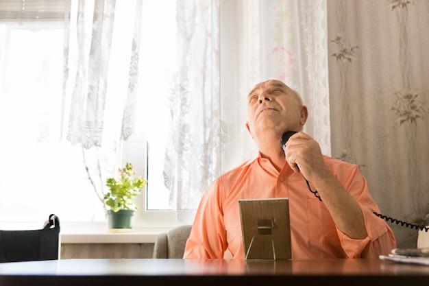 오렌지 셔츠에 앉아 있는 노인이 위로 향하는 동안 전기 면도기를 사용하여 목에 머리카락을 면도