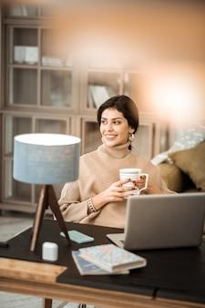 Сидя на кресле. красивая мирная дама в бежевом вязаном свитере в домашнем шкафу с раздетой чашкой кофе