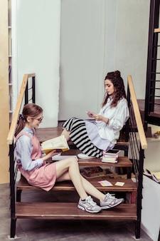 床に座っています。一緒に木製の階段に座って本や資料を読んで忙しい集中女性