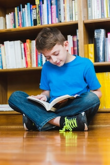 Sitting on floor excited boy reading book