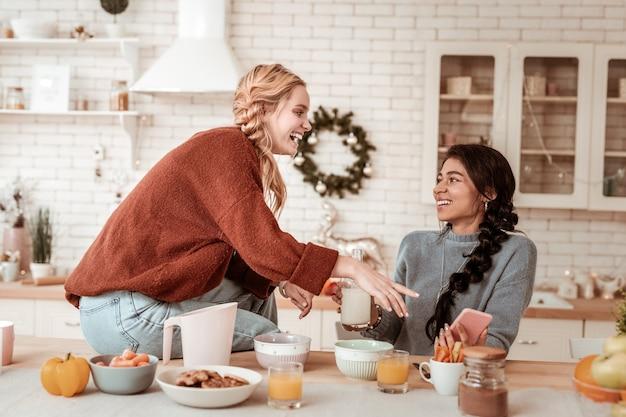 テーブルの上に座っています。彼女は陽気な写真を見せながら彼女の友人のスマートフォンを指している明るい髪の少女を笑う