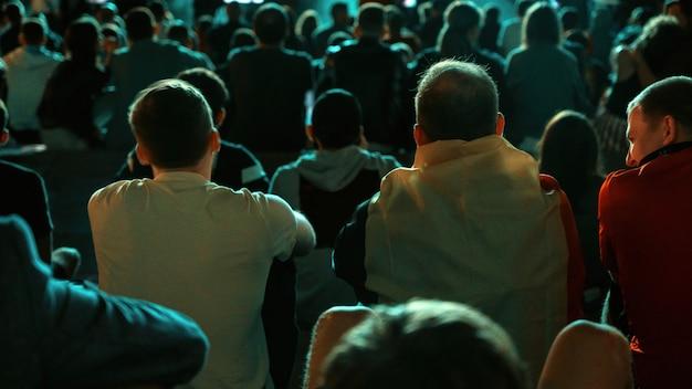 夜に公共の場所でサッカーを見ている人々を座って