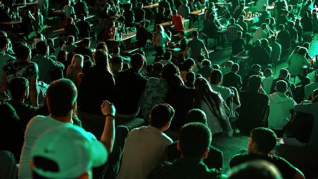 Persone sedute a guardare il calcio in un luogo pubblico di notte