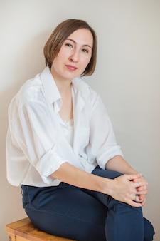 Сидя улыбается бизнес европейская женщина в белой рубашке