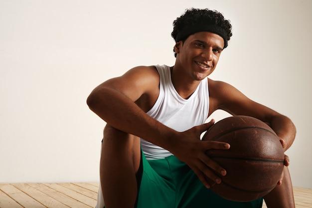 茶色の革のボールを保持している白と緑のユニフォームを着てアフロと笑顔のフレンドリーなアフリカ系アメリカ人のバスケットボール選手に座って