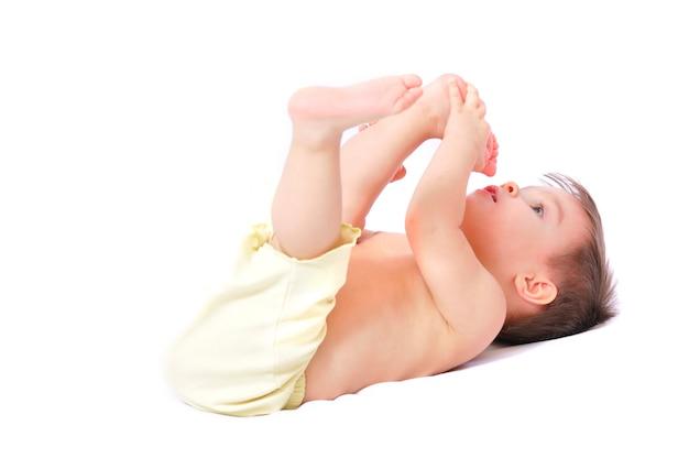 つま先を持って楽しい黄色のショートパンツで笑顔の幸せな小さな1歳の女の赤ちゃんに座っています。