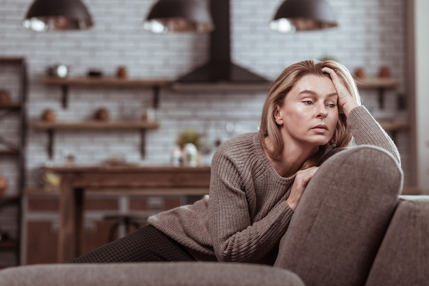 Sitting on sofa. mature family woman sitting on the sofa in the living room and feeling stressed