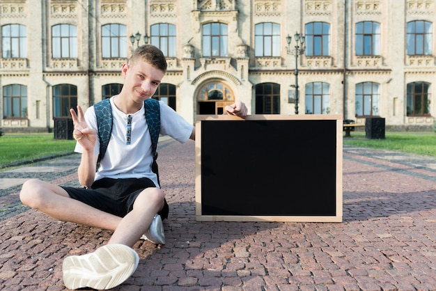 Sitting teenage boy holding  blackboard