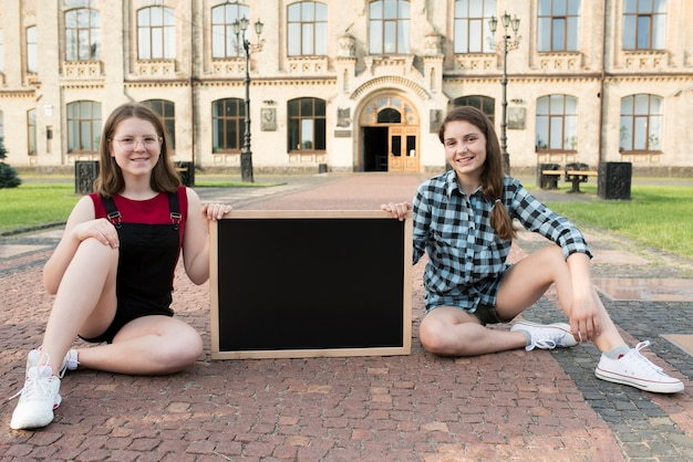 Sitting teenage girls holding blackboard